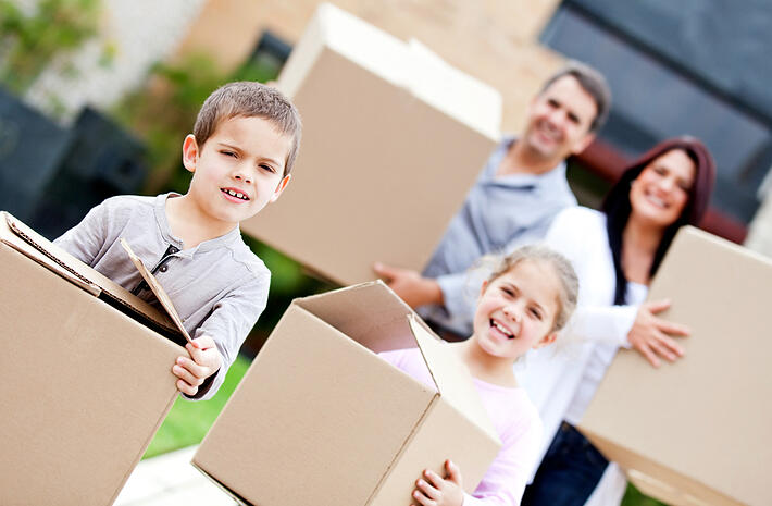 Family moving home and carrying cardboard boxes