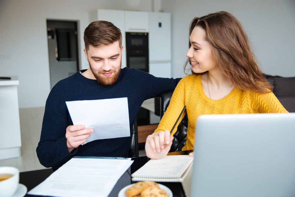 Happy young couple calculating bills at home-2