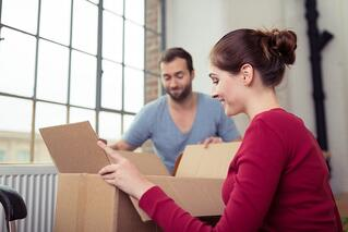 Attractive young couple moving house getting ready to unpack a cardboard carton of personal possessions below a big window.jpeg