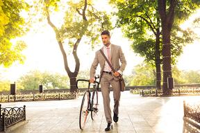 Confident young businessman walking with bicycle on the street in town .jpeg
