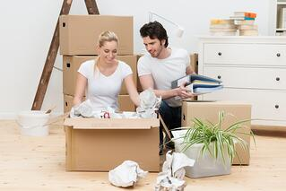 Happy young couple unpacking in their new home kneeling on a bare wooden floor unwrapping items from a large brown cardboard box.jpeg