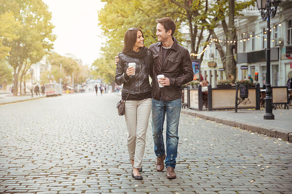 Portrait of a happy romantic couple with coffee walking outdoors in old european city-1