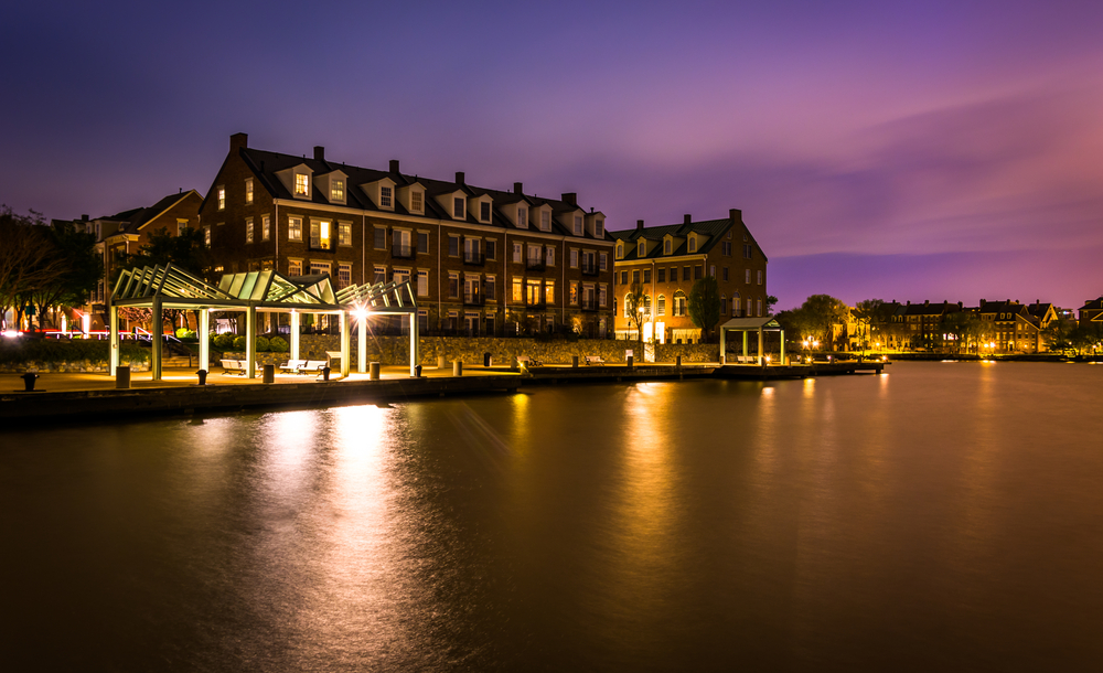 Waterfront condominiums and promenade along the Potomac River at night in Alexandria, Virginia.